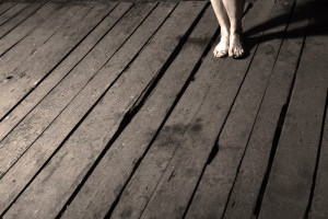 Woman's bare feet on old wooden floor